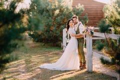 Stilvolle romantische Paare, die auf Ranch stehen und umarmen stockbild