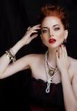 Stilvolle Rothaarigefrau der Schönheit mit Frisur und stockfoto