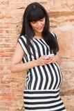 Stilvolle schwangere Frau, die am Telefon simst Stockfotos
