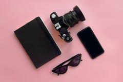Stilvolle schwarze Sonnenbrille, Smartphone, Fotokamera und Notizbuch an Stockfotografie