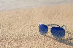 Stilvolle Sonnenbrille auf dem Strand Lizenzfreie Stockbilder