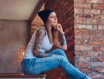 Stilvolle tattoed blonde Frau im T-Shirt und in den Jeans Lizenzfreie Stockfotografie