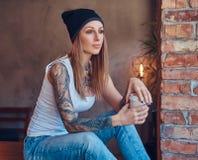 Stilvolle tattoed blonde Frau im T-Shirt und in den Jeans Stockfoto