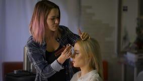 Stilvolle Vorlagenfrisur mit dem rosa Haar Frisur für die attraktive Blondine in einem Schönheitssalon stock footage