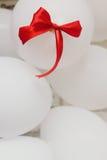 Stilvolle weiße Ballone mit rotem Bogen auf ihnen an der Hochzeitszeremonie Stockfotografie