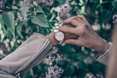 Stilvolle weiße Uhr auf Frauenhand Stockbild