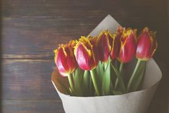 Stilvolle Weinleseblumenstraußzusammensetzung mit Bifarbtulpen auf dunkelbraunem Holztisch Zweifarbige Blumen eingewickelt im Pap stockfoto