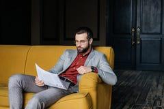 stilvolle Zeitung und -sitzen des gutaussehenden Mannes Lese Lizenzfreies Stockbild