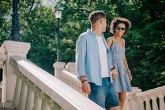 stilvolle zwischen verschiedenen Rassen Paare in der Sonnenbrille, die die Treppe hinunter geht stockfotografie