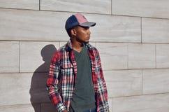 Stilvoller afrikanischer Mann, der rotes kariertes Hemd, Baseballmütze, weg schauend, junger Kerl trägt, der auf Stadtstraße, gra stockbild