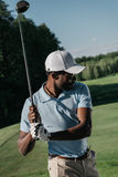 Stilvoller Afroamerikanermann, der Golf am Golfplatz spielt stockfotografie