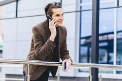 stilvoller attraktiver Kerl in der Jacke mit Telefonpaß und -karten stockfotos