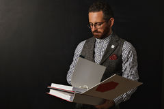 Stilvoller bärtiger Lehrer mit Mappen an der Tafel lizenzfreie stockfotos