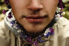 Stilvoller blonder Hippie mit Bart mit Blumen auf dem Hintergrund Stockfotos