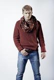 Stilvoller blonder Mann in der Strickjacke, im Schal und in den Jeans Lizenzfreies Stockfoto