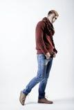 Stilvoller blonder Mann in der Strickjacke, im Schal und in den Jeans Stockbild
