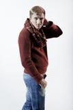 Stilvoller blonder Mann in der Strickjacke, im Schal und in den Jeans Stockfotos