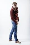 Stilvoller blonder Mann in der Strickjacke, im Schal und in den Jeans Lizenzfreies Stockbild