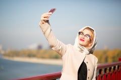 Stilvoller blonder vorbildlicher Tourist, der selfie am intelligenten Telefon nimmt Frau Lizenzfreie Stockfotos