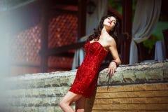 Stilvoller Brunette im roten Kleid auf Natur Stockbild