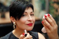 Stilvoller Brunette kürzte Frauenfarbenlippen auf der Straße ab, die im Spiegel schaut stockfotos