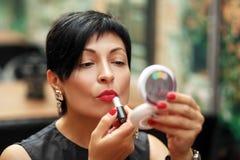 Stilvoller Brunette kürzte Frauenfarbenlippen auf der Straße ab, die im Spiegel schaut lizenzfreie stockbilder