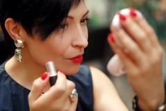 Stilvoller Brunette kürzte Frauenfarbenlippen auf der Straße ab, die im Spiegel schaut lizenzfreies stockfoto