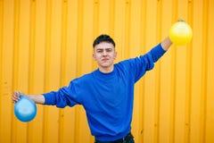Stilvoller ernster Kerl in einer blauen Strickjacke, mit gelbem und blauem infl Stockfotografie