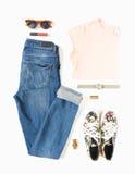 Stilvoller Frauenblick Frauen-/Mädchenausstattung auf weißem Hintergrund Blaue Denimjeans, Pfirsicht-shirt, Blumendruckturnschuhe lizenzfreie stockfotografie