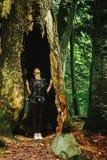 Stilvoller Frauenhippie-Reisender, der erstaunlichen Baum mit Loch betrachtet Stockfoto