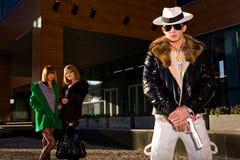 Stilvoller Gangster mit einer Gewehr und zwei jungen Frauen Lizenzfreies Stockfoto
