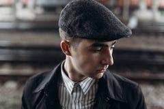 Stilvoller Gangstermann, der auf Hintergrund der Eisenbahn aufwirft England herein Lizenzfreie Stockfotografie