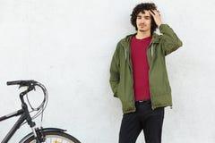 Stilvoller gelockter Mann trägt schwarze Hose, grünen Anorak, steht nahe Fahrrad gegen weißen Hintergrund, Gleichreitfahrrad, hat stockfoto