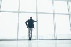 Stilvoller Geschäftsmann im Hintergrund eines großen Fensters Stockbild