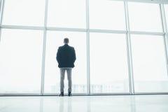 Stilvoller Geschäftsmann im Hintergrund eines großen Fensters Stockbilder