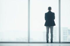 Stilvoller Geschäftsmann im Hintergrund eines großen Fensters im Büro Lizenzfreie Stockfotos
