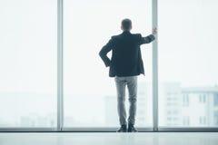 Stilvoller Geschäftsmann im Hintergrund eines großen Fensters im Büro Lizenzfreies Stockbild