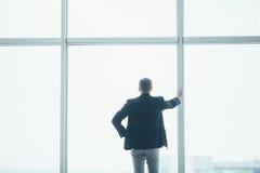 Stilvoller Geschäftsmann im Hintergrund eines großen Fensters im Büro Lizenzfreie Stockbilder