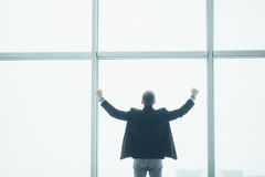 Stilvoller Geschäftsmann in rised Handsieg im Hintergrund eines großen Fensters Stockbild