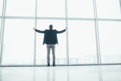 Stilvoller Geschäftsmann in rised Handsieg im Hintergrund eines großen Fensters Stockfotos