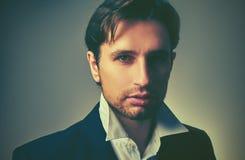 Stilvoller gutaussehender Mann in einer Klage in der Dunkelheit Stockbild