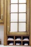 Stilvoller hölzerner Schrank mit Regalen mit weißen Tüchern im kitche Lizenzfreie Stockfotografie