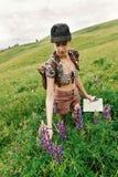 Stilvoller Hippie-Frauenreisender, der in der Hand Karte und wildflowe hält Stockfoto