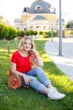 Stilvoller Jugendlicher weared in den Jeans und in rotem T-Shirt, die auf Gras sitzen stockfotografie
