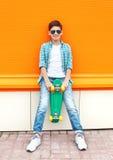 Stilvoller Jugendlichjunge, der ein kariertes Hemd, Sonnenbrille und Skateboard in der Stadt trägt Stockfoto