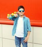 Stilvoller Jugendlichjunge, der ein kariertes Hemd und Sonnenbrille mit Skateboard in der Stadt trägt Stockfotografie