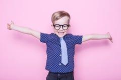 Stilvoller Junge im Hemd und in den Gläsern mit großem Lächeln schule vortraining Art und Weise Studioporträt über rosa Hintergru lizenzfreie stockfotos
