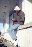 Stilvoller junger afrikanischer Mann des Lebensstils, der Smartphone in der Stadt verwendet stockfotos