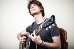 Stilvoller junger blonder Hippie-Mann, der Gitarre spielt Stockbild
