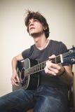 Stilvoller junger blonder Hippie-Mann, der Gitarre spielt Lizenzfreies Stockfoto